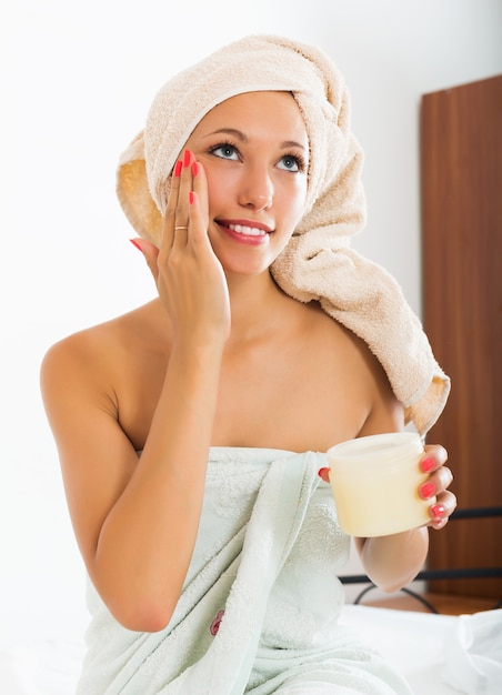 Woman putting cream on face Free Photo