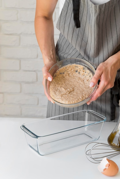 Woman putting dough in cake mould Free Photo