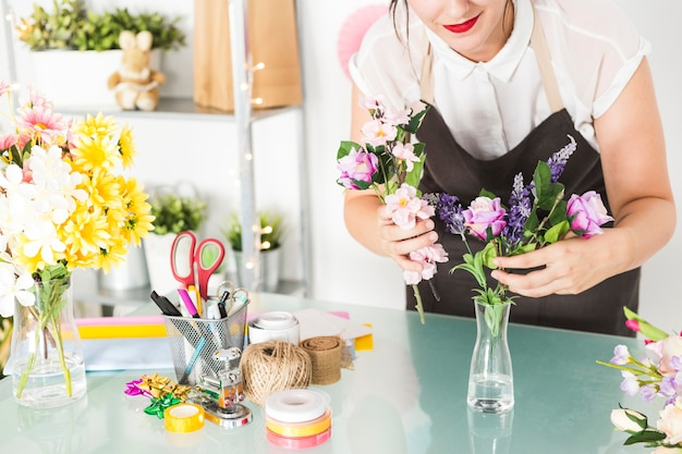 Hey! Remember you have to attribute freepik & Woman putting flowers in vase on glass desk Photo | Free Download