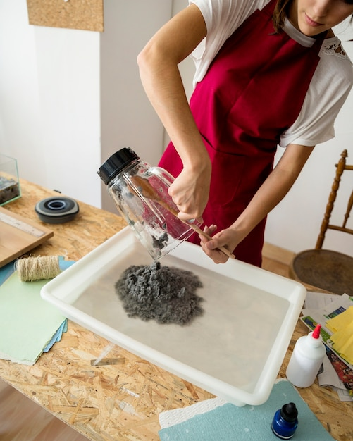 Woman putting grinded paper pulp in water over wooden desk Free Photo