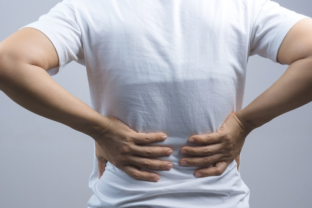 Woman putting her hands for back or spine pain Premium Photo