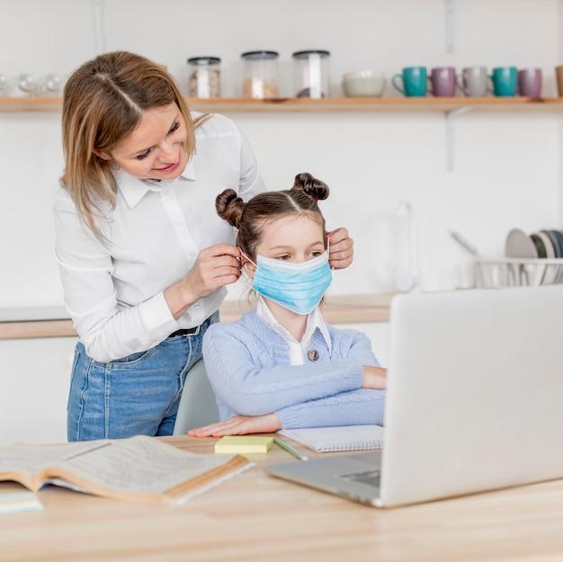 Donna che mette una mascherina medica su sua figlia Foto Gratuite