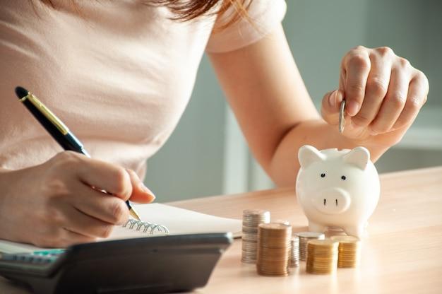 Woman putting money in a piggy bank Premium Photo