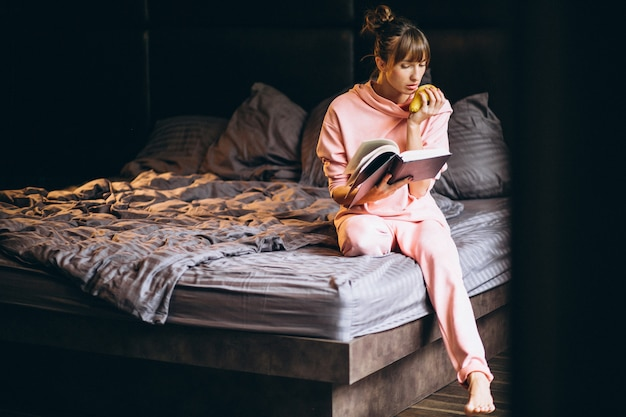 Woman in pygama sitting in bed and reading book Free Photo