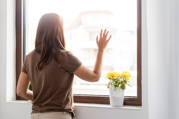 Donna in quarantena a casa guardando attraverso la finestra Foto Gratuite