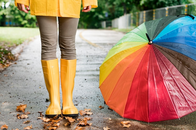 Woman in rain boots standing next to colorful umbrella Free Photo