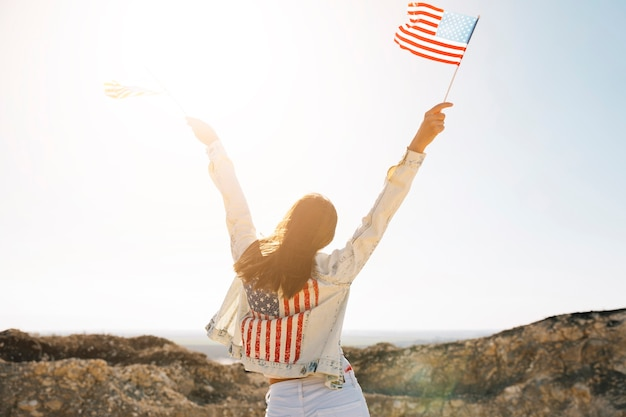 Woman raising hands with flags on mountain Free Photo