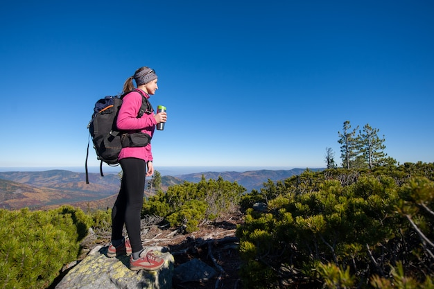 Woman reaching her goal standing on peak of the mountain Premium Photo
