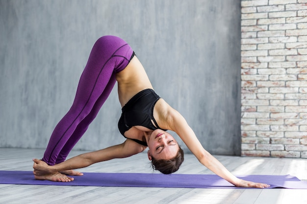 Woman reaching her leg while standing in a downward-facing dog pose Free Photo
