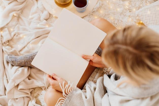 冬休みを楽しみながら本を読む女性 無料写真