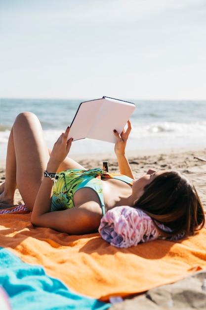 Женщина читает книгу на пляже Бесплатные Фотографии