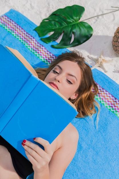 Woman reading book on beach Free Photo