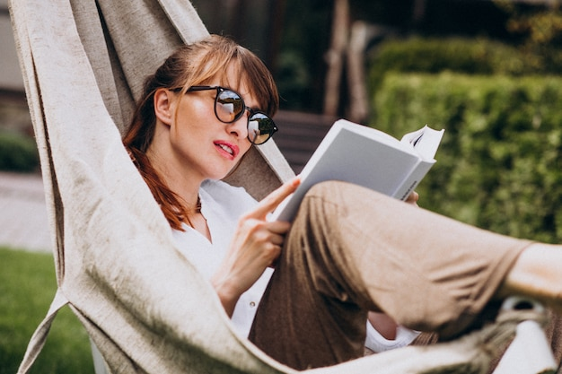Woman reading a book in the garden by the house Free Photo