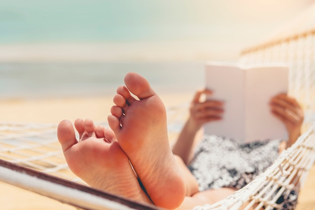 Woman reading a book on hammock beach in free time summer holiday Premium Photo