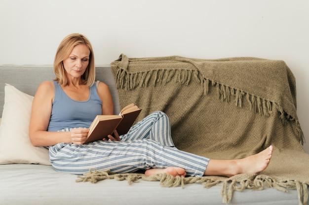 Libro di lettura della donna a casa durante la quarantena Foto Gratuite