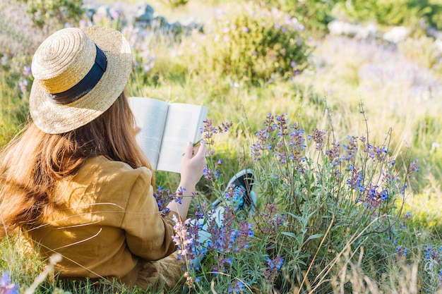 Woman reading a book in nature surrounded by vegetation and flowers Premium Photo