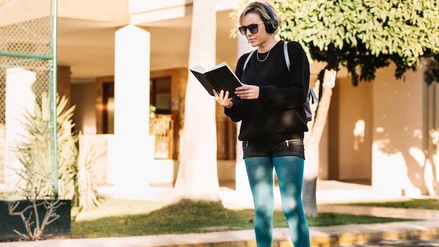 Woman reading book on street Free Photo