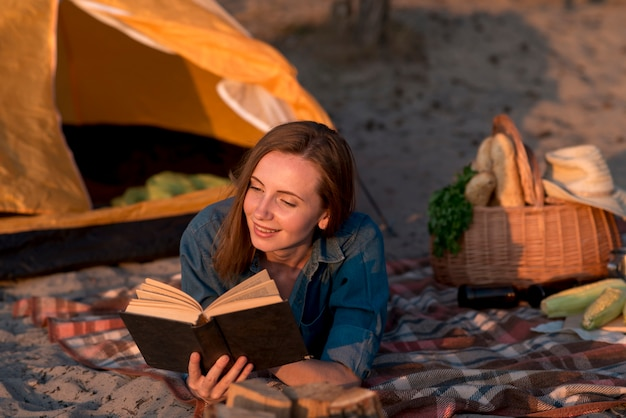 Woman reading a book on picnic blanket Free Photo