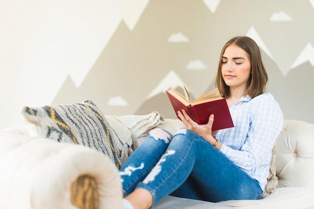 1e9eaf80b67e Woman reading book on sofa in living room Free Photo