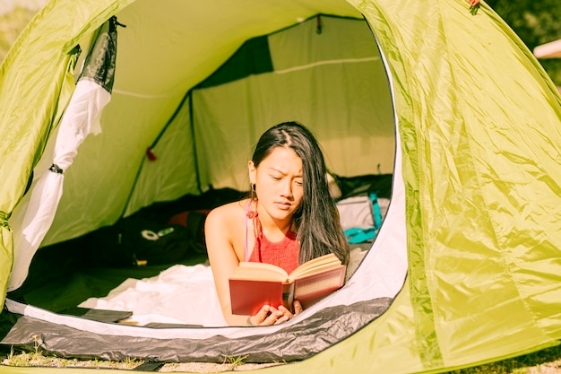 Woman reading book in tent Free Photo