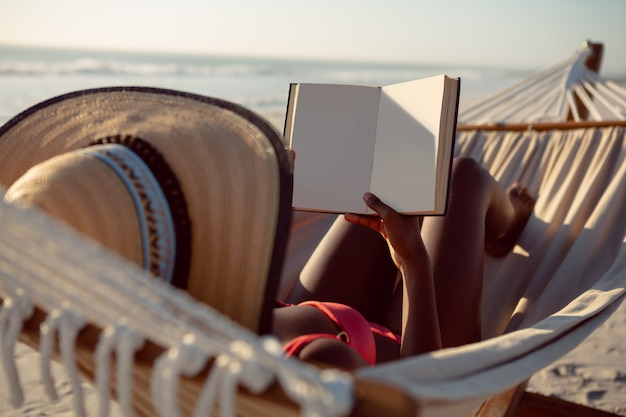 Woman reading a book while relaxing in hammock on the beach Free Photo