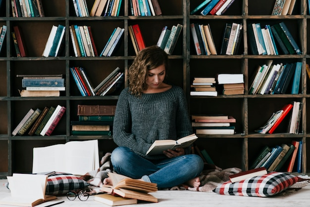 Woman reading on floor near bookshelf Free Photo