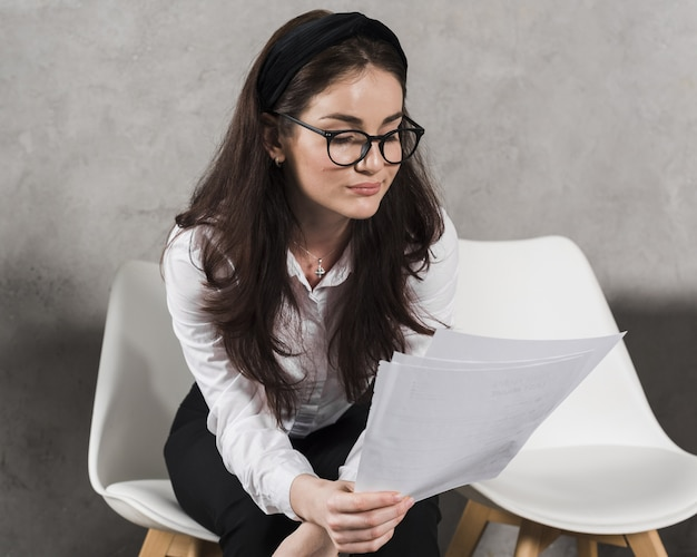 Woman reading her resume before attending a job interview Free Photo
