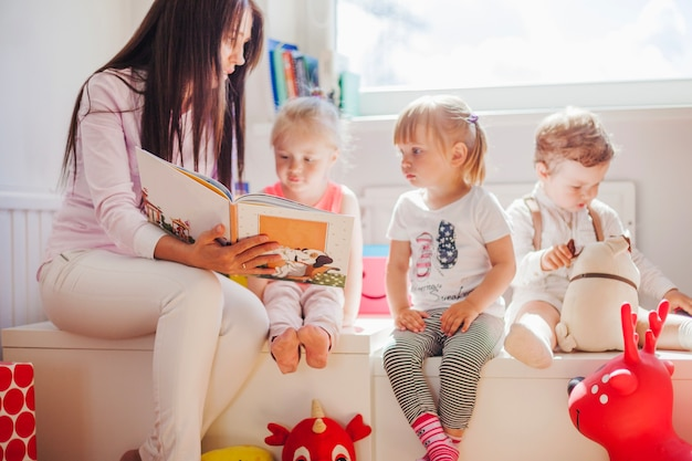 Woman reading to kids in school Free Photo