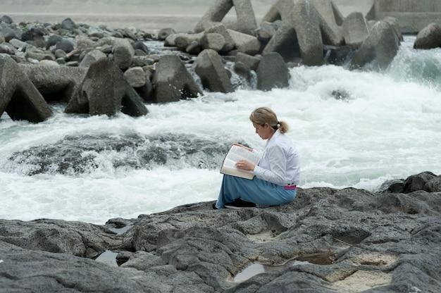Женщина читает библию, сидя на берегу реки фудзикава в городе фудзи, япония. Premium Фотографии