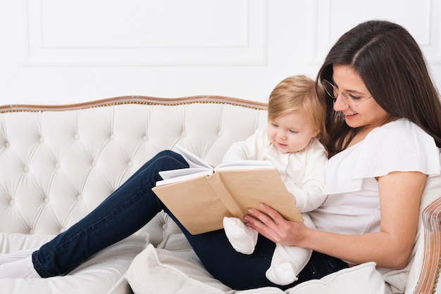 Woman reading with baby on sofa Free Photo