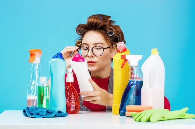 Женщина читает детали на бутылке во время работы по дому, она выглядит усталой Бесплатные Фотографии