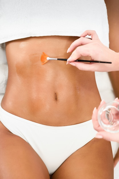 Woman receiving belly massage treatment with oil brush Free Photo