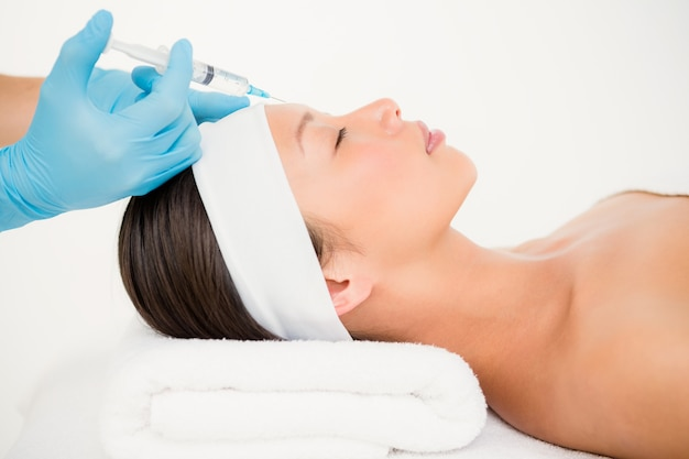 Woman receiving botox injection on her forehead Premium Photo