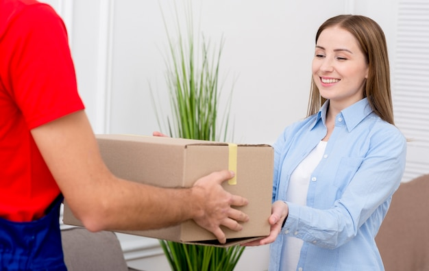 Woman receiving a cardboard box from courier Premium Photo