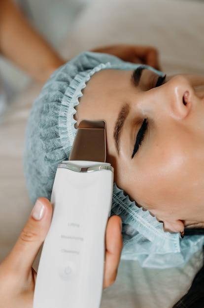 Женщина, получающая электрический пилинг лица ультразвуком в салоне красоты. Premium Фотографии