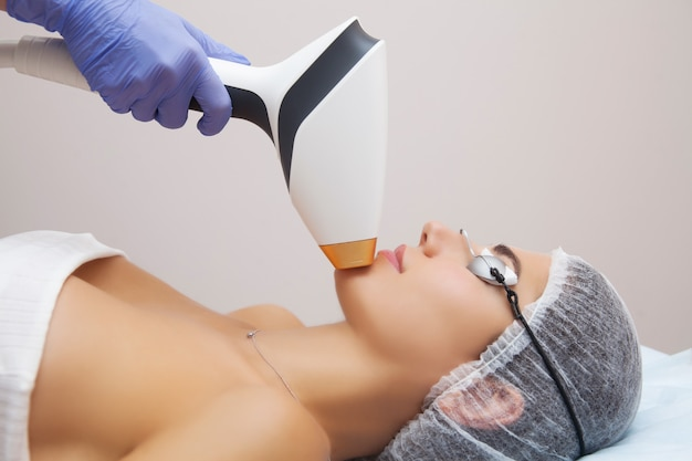 Woman receiving facial beauty treatment, removing pigmentation at cosmetic clinic. Premium Photo