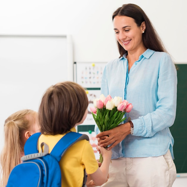 Woman receiving flowers from her students Free Photo
