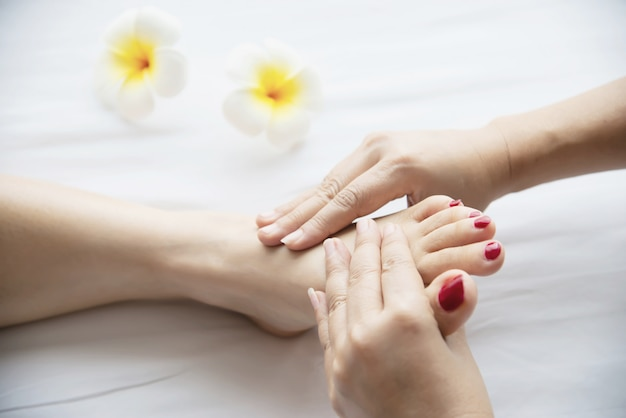 Woman receiving foot massage service from masseuse close up at hand and foot - relax in foot massage therapy service concept Free Photo
