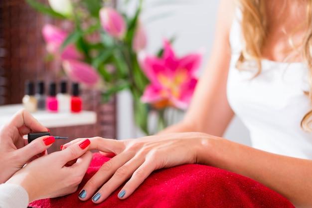Woman receiving manicure in nail salon Premium Photo