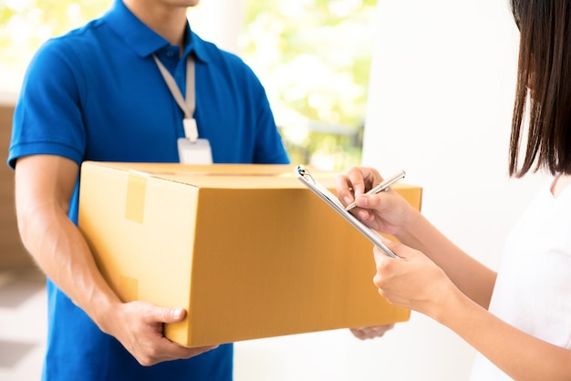 Woman receiving parcel from a delivery man Premium Photo