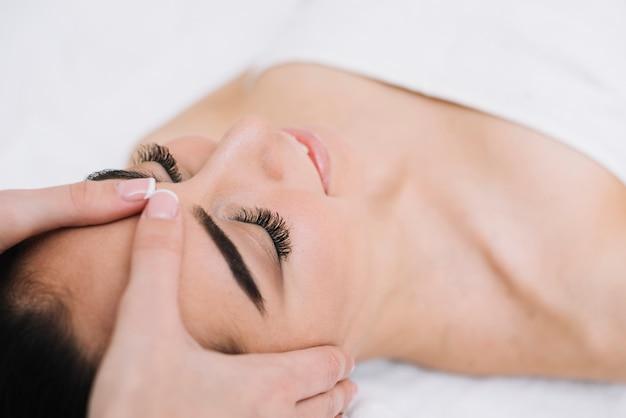 Woman receiving a relaxing facial massage Free Photo