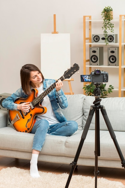 Женщина перекодирует себя во время игры на гитаре Бесплатные Фотографии