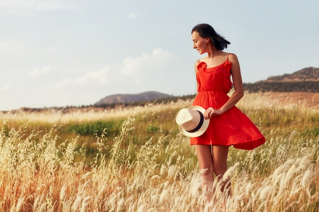 Woman in a red dress walking on the field  summer Premium Photo