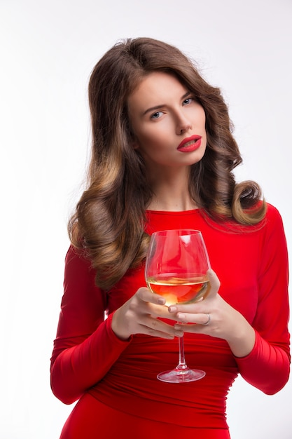 Woman in red gown with champagne glass on white Premium Photo