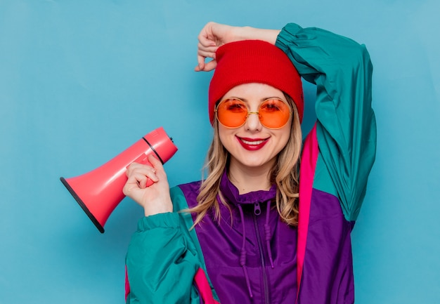 Woman in red hat, sunglasses and suit of 90s with loudspeaker Premium Photo