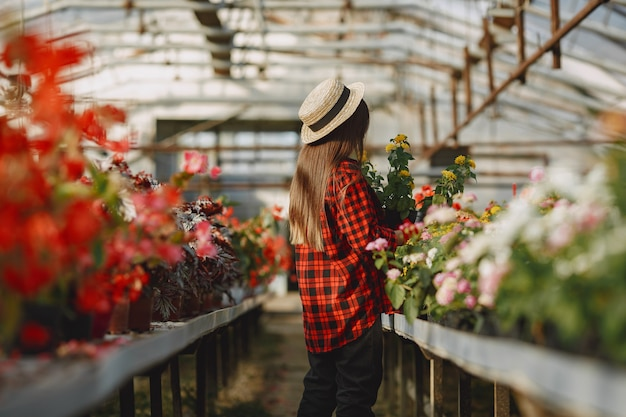 Woman in a red shirt. worker with flowerpoots. daughter with plants Free Photo