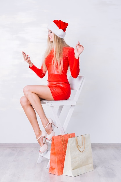 Woman in red sitting on chair with phone Free Photo