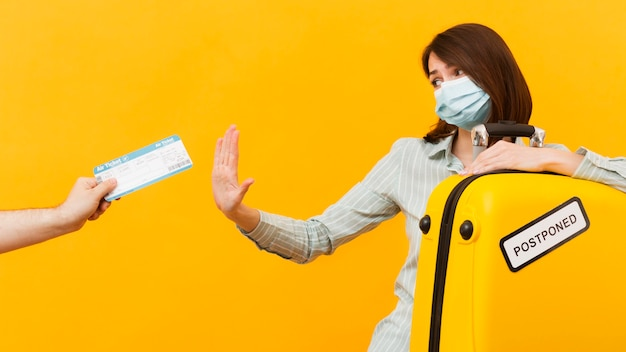 Woman rejecting a plane ticket while wearing e medical mask Free Photo