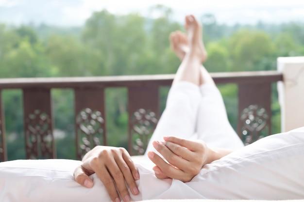 女性はベッドでリラックスし、山の景色を楽しんでいます。 Premium写真