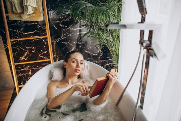 Donna che si distende nella vasca da bagno con le bolle Foto Gratuite